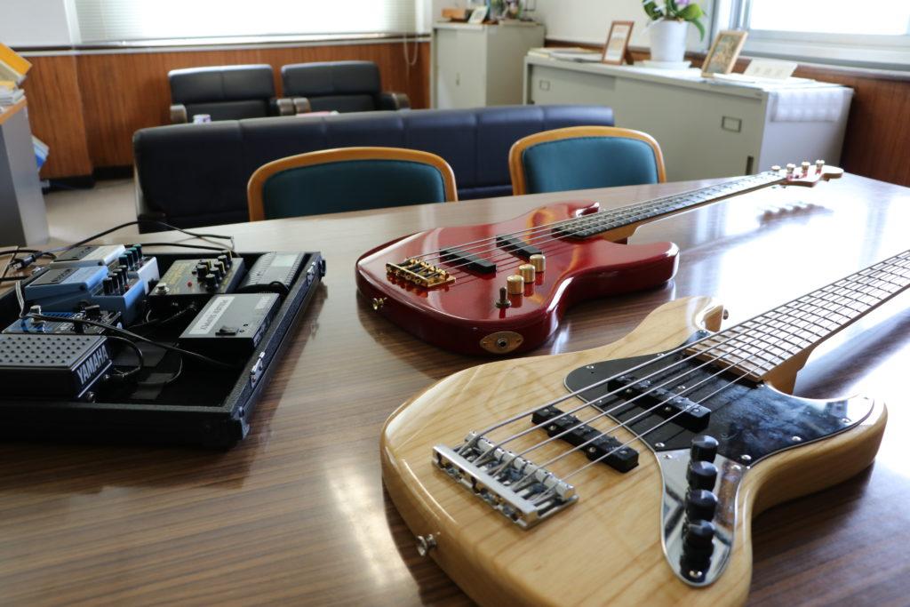 校長室の机に並ぶベースギターとエフェクター
